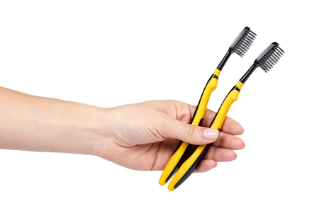 Black and yellow soft toothbrush with hand isolated on white background.