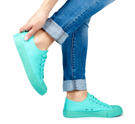 Female leg in jeans and sneakers isolated on white background.