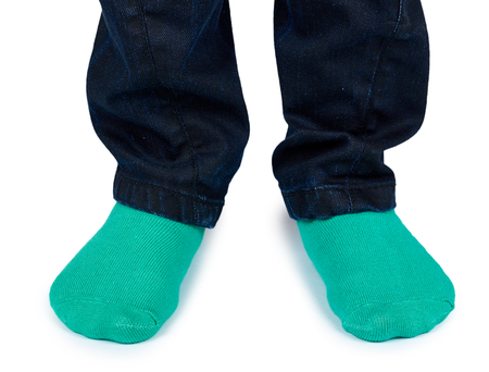 Kid legs in colored socks on leg isolated on white background.