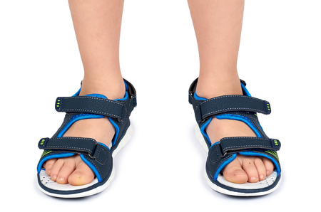 Kids leather sandals on leg isolated on a white background. Standard-Bild