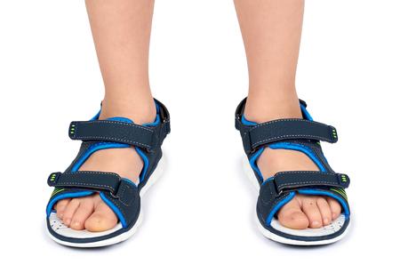Sandali in pelle per bambini sulla gamba isolata su uno sfondo bianco.