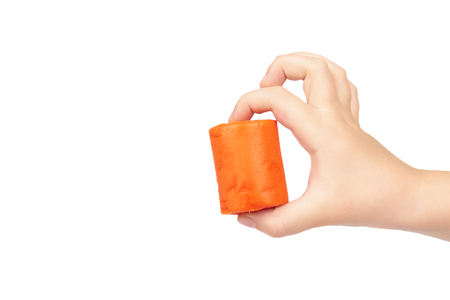 Orange plasticine bar with kid hand, isolated on white background. copy space template.