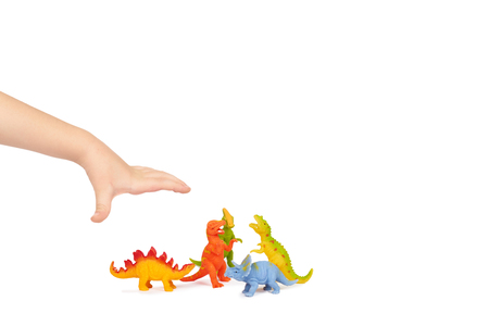 Prehistoric dinosaur rubber toy with kid hand, isolated on white background. copy space template.