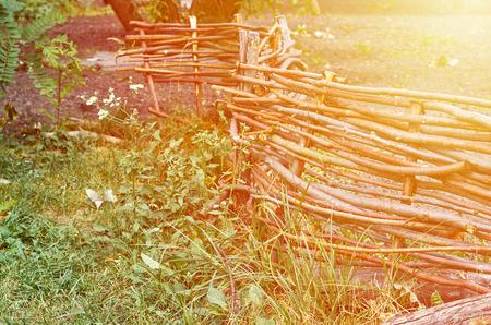 Rustic wicker fence closeup background, sunlight. Stock Photo