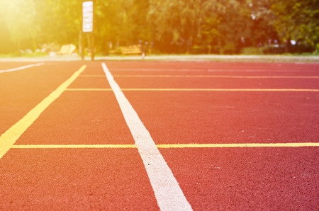 Decorative rubberized Jogging coating at the street stadium in outdoor with white line. Sport Background with sunlight effect. Stock fotó