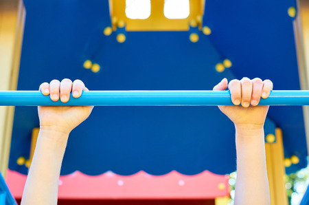 sports horizontal bar for children in the public playground, with kids hand.