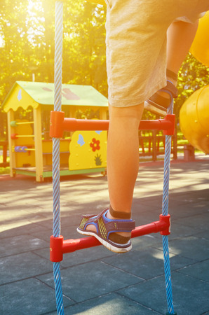 sports rope ladder for children in the public playground, with kids leg, sunlight effect. Stock Photo