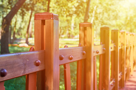 wooden decorative fence in the city park, sunlight effect.