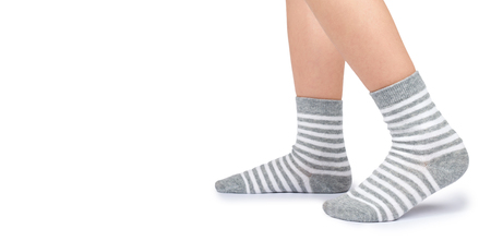 Kid legs in striped socks isolated on white background, copy space template. Zdjęcie Seryjne - 107189155