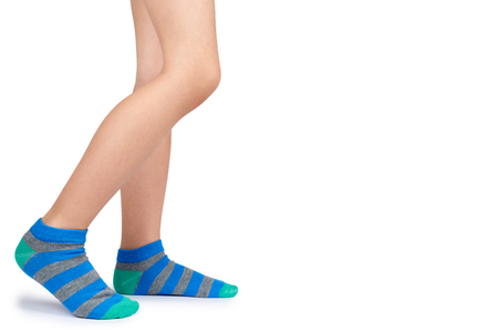 Kid legs in striped socks isolated on white background, copy space template. Stockfoto