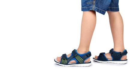 Kids leather sandals on leg isolated on a white background, copy space template. Stock Photo