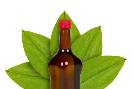 Bottle of dark soy or balsamic sauce on the background of leaves. Isolated on white. Asian food, japanese organic seasoning.
