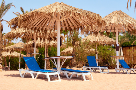 umbrellas for sun protection and sun beds on the sandy beach. Stock Photo