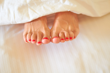 legs of the girl lie on a bed on a white sheet, rest and relaxation.