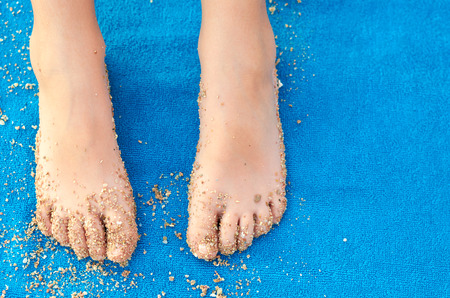 Blue fabric texture of soft towel with sand and kids leg, macro photo.