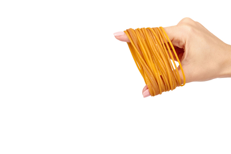 Yellow rubber bands close up with hand isolated on white background, copy space template Stock Photo
