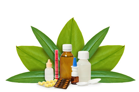 Bottle with medicine, pills on the background of green leaves. Isolated on white. concept of natural origin. Stock Photo