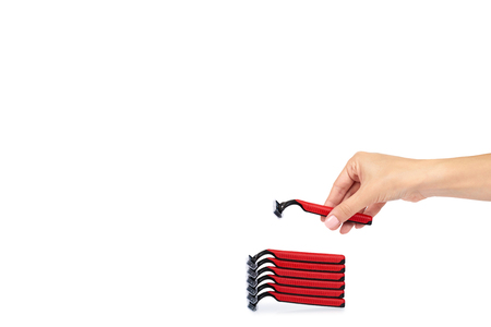 Red disposable shaving razor with hand isolated on white background, copy space template