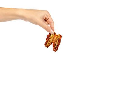 Sun dried red tomatoes with hand isolated on white background, copy space template. Stock Photo