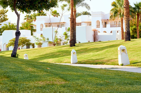 white buildings on a background of green grass and palms.