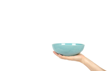 Blue empty ceramic bowl with hand isolated on white background, copy space template. Stock Photo