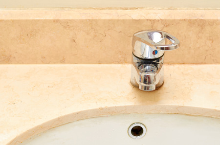 marble sink with chromed faucet, bathroom background.
