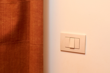 white light switch on the wall in the room.