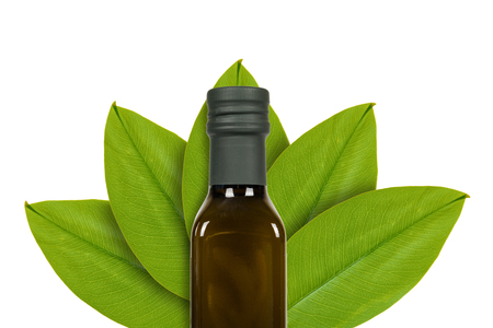 Green bottle of olive oil on the background of green leaves. Isolated on white. concept of natural origin