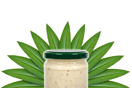Creamy sauce with truffle for pasta in glass jar on the background of green leaves. Isolated on white. concept of natural origin. Stock Photo