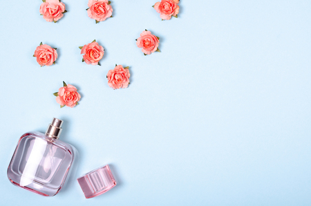 Flat lay arrangement of perfume bottle and flowers for mock up design, table top view image of decoration valentines day background concept for post card