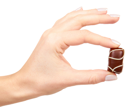 Hand with chocolate candy sweet dessert closeup. Isolated on white background