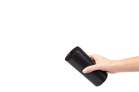 hand with roll of black plastic garbage bags for trash. Isolated on white background. Copy space Stock Photo - 120144503