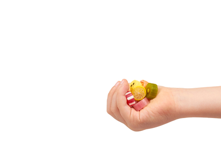 Kids hand with colored round candy, sugar lollipop. Isolated on white background. Copy space Stock Photo