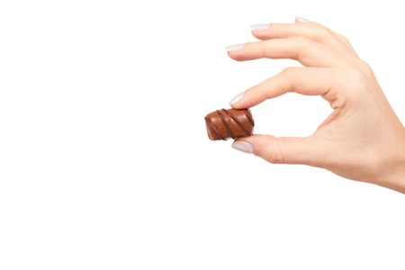 Hand with chocolate candy sweet dessert closeup. Isolated on white background. Copy space Stock Photo - 120144508