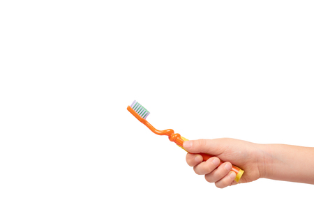 Kids hand with orange toothbrush, dental care concept. Isolated on white background. Copy space