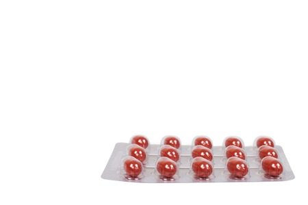 red vitamin capsule in blister, medicine dupplement. Isolated on white background. Copy space