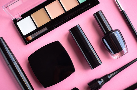 Different makeup products composition on pink background, flat lay and top view photo