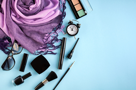 Different makeup products composition on blue background, flat lay and top view photo