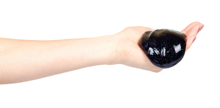Hand with black slime toy for kids, glitters and goo. Isolated on white background
