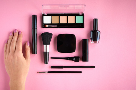 Different makeup products composition with hand on pink background, flat lay and top view photo