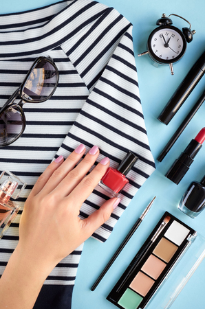 Different makeup products composition with hand on blue background, flat lay and top view photo Stock Photo