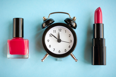 Black alarm clock composition with cosmetics on blue background, flat lay and top view photo