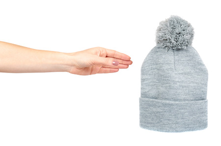 Hand with gray knitted hat, warm woolen accessory. Isolated on white background