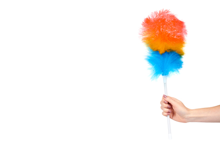 Hand with soft colorful duster, synthetic feather broom, fluffy cleaner. Isolated on white background. Copy space template Standard-Bild