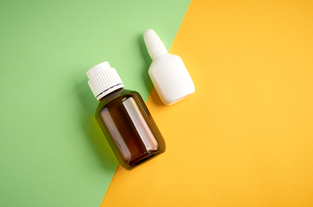 Nasal spray bottle composition, white template bottle on yellow and green background, flat lay and top view photo Stock Photo