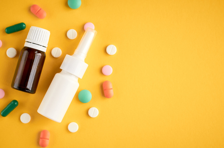 Nasal spray bottle with pills composition, white template bottle on yellow background, flat lay and top view photo
