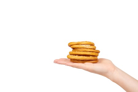 Mano con bagel essiccato, panino appena sfornato, snack fast food. Isolato su sfondo bianco. Copia modello di spazio Archivio Fotografico