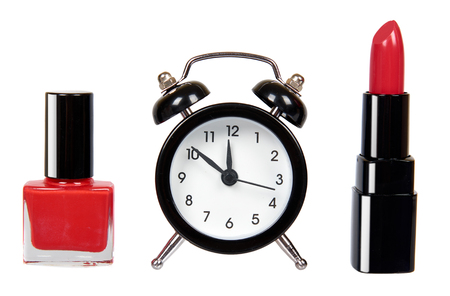 Red nail polish, lipstock and alarm clock. Isolated on white background