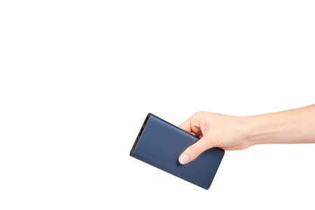 Hand with dark blue power bank for charging mobile devices, external battery. Isolated on white background. Copy space template Reklamní fotografie