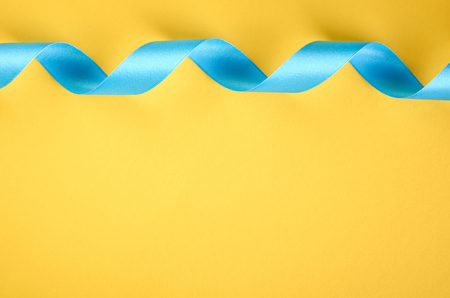 Blue ribbon on yellow background composition, flat lay and top view photo